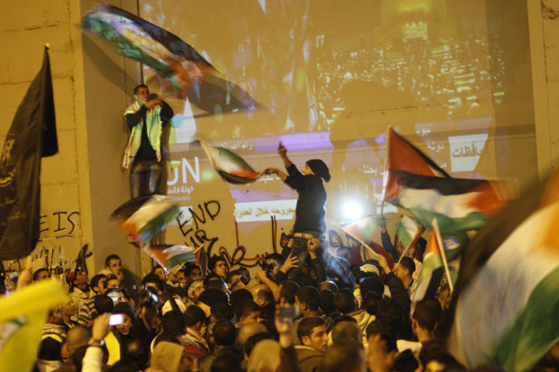 Palestinians celebrate next to a section of Israeli separation barrier at the entrance to the west bank city of Bethlehem as they watch a screen showing the U.N. General Assembly votes on a resolution to upgrade the status of the Palestinian Authority to a nonmember observer state, Thursday, Nov. 29, 2012.  The U.N. General Assembly has voted by a more than two-thirds majority to recognize the state of Palestine. The resolution upgrading the Palestinians' status to a nonmember observer state at the United Nations was approved by the 193-member world body late Thursday by a vote of 138-9 with 41 abstentions. (AP Photo/Nasser Shiyoukhi)