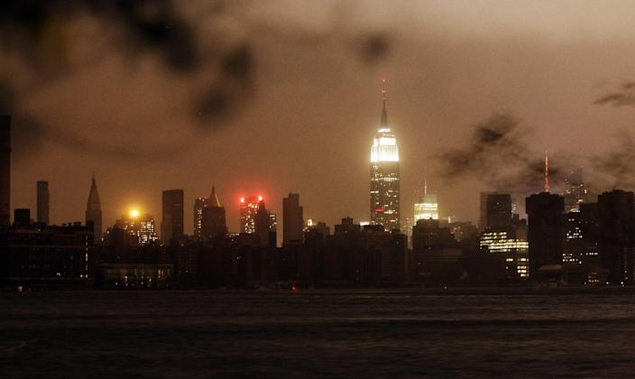 The New York skyline remains dark Monday, Oct. 29, 2012, as seen from the Williamsburg neighborhood in the Brooklyn borough of New York. In an attempt to lessen damage from saltwater to the subway system and the electrical network beneath the city's financial district, New York City's main utility cut power to about 6,500 customers in lower Manhattan. But a far wider swath of the city was hit with blackouts caused by flooding and transformer explosions. (AP Photo/Frank Franklin II)