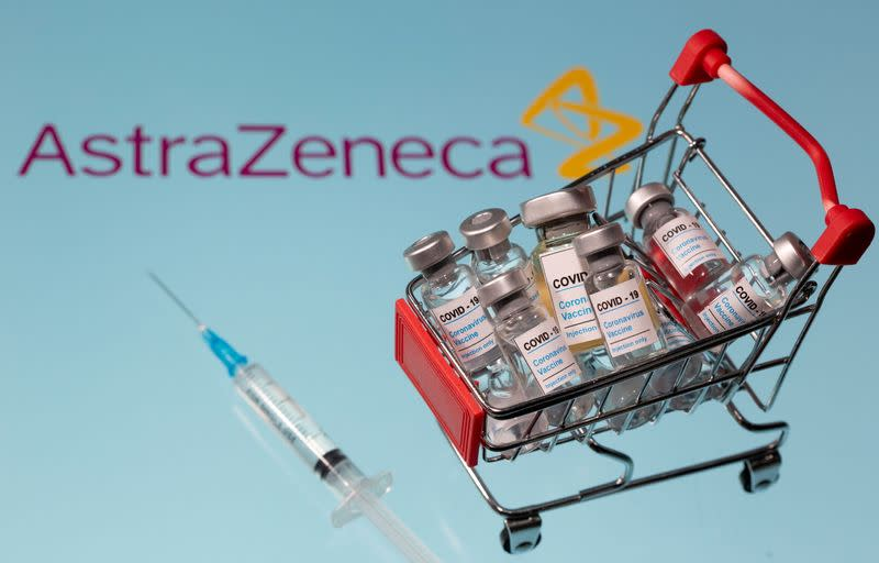 """FILE PHOTO: A small shopping basket filled with vials labeled """"COVID-19 - Coronavirus Vaccine"""" and a medical sryinge are placed on a AstraZeneca logo"""