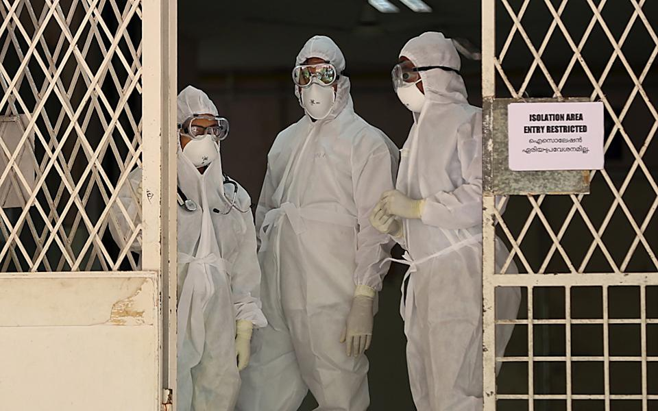 Medical staff wearing full protective suits stand at the entrance to the isolated ward of the Ernakulam Government Medical College in Kochi, Kerala, India. Source: EPA via AAP