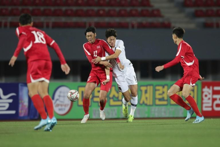 South Korea's Hwang Ui-jo and North Korea's Ri Yong Jik fight for the ball during the World Cup 2022 Qualifying match in Pyongyang (AFP Photo/handout)