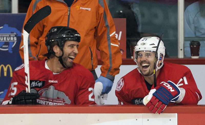 Philadelphia Flyers' Maxime Talbot, left, and Montreal Canadiens' Brian Gionta laugh while sitting on the bench during the first period of a charity hockey game in Chateauguay, Quebec, Thursday, Sept. 27, 2012. The NHL canceled the rest of the preseason Thursday, just a day before negotiations were set to resume in an effort to end the lockout. (AP Photo/The Canadian Press, Graham Hughes)