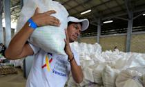 What happens to the sea of shiny white plastic bags filled with vital supplies now hinges on the military