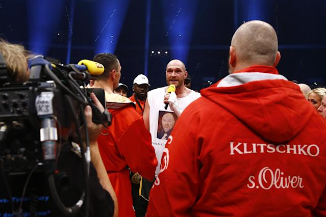 Boxing - Wladimir Klitschko v Tyson Fury WBA, IBF & WBO Heavyweight Title's - Esprit Arena, Dusseldorf, Germany - 28/11/15 Tyson Fury sings with the microphone as he celebrates winning the fight while Wladimir Klitschko looks on Reuters / Kai Pfaffenbach Livepic
