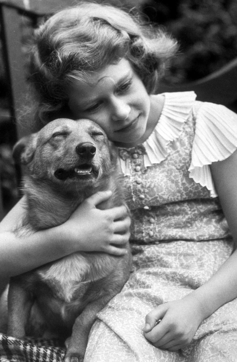 Queen Elizabeth II hugging Dookie, her first-ever corgi, 1936.