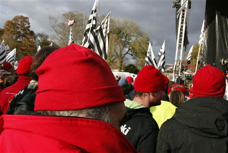 "Protesters wearing red caps, the symbol of protest in Brittany take part in a demonstration to maintain jobs in the region and against an ""ecotax"" on commercial trucks, in Carhaix, western France, November 30, 2013. REUTERS/Mal Langsdon"