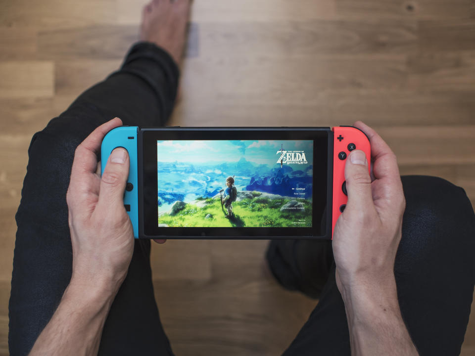 Gothenburg, Sweden - March 10, 2017: A shot from above of a young man's hands holding a neon coloured Nintendo Switch video game system developed and released by Nintendo Co., Ltd. in 2017. The system is turned on and the game The Legend of Zelda, Breath of the Wild is showing on the display. Shot on a hardwood floor background in a home environment.