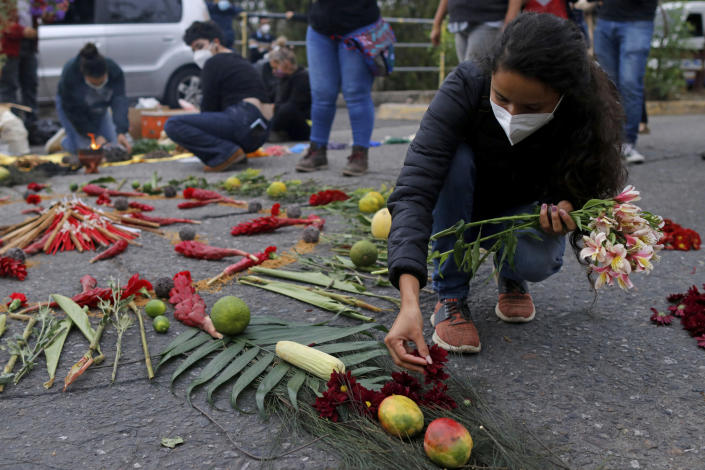 Berta Zuniga, a daughter of environmental and Indigenous rights activist Berta Caceres, places flower petal on an offering at a spiritual ceremony, a day before a trial against one of the alleged masterminds of the killing of Caceres, in Tegucigalpa, Honduras, Monday, April 5, 2021. The trial of Roberto David Castillo is expected to run through April. The government has already convicted seven people in Caceres' murder, but is Castillo is considered a potentially critical link to those who ordered it. (AP Photo/Elmer Martinez)