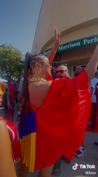 Lizzo wearing a multicolored wide-sleeved dress as she waves to fans