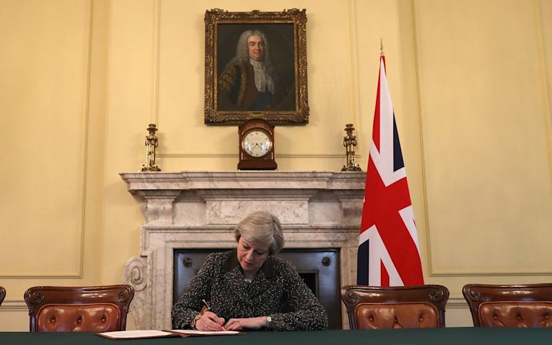 A Union flag was at Theresa May's side as she signed the historic eltter - Getty Images Europe