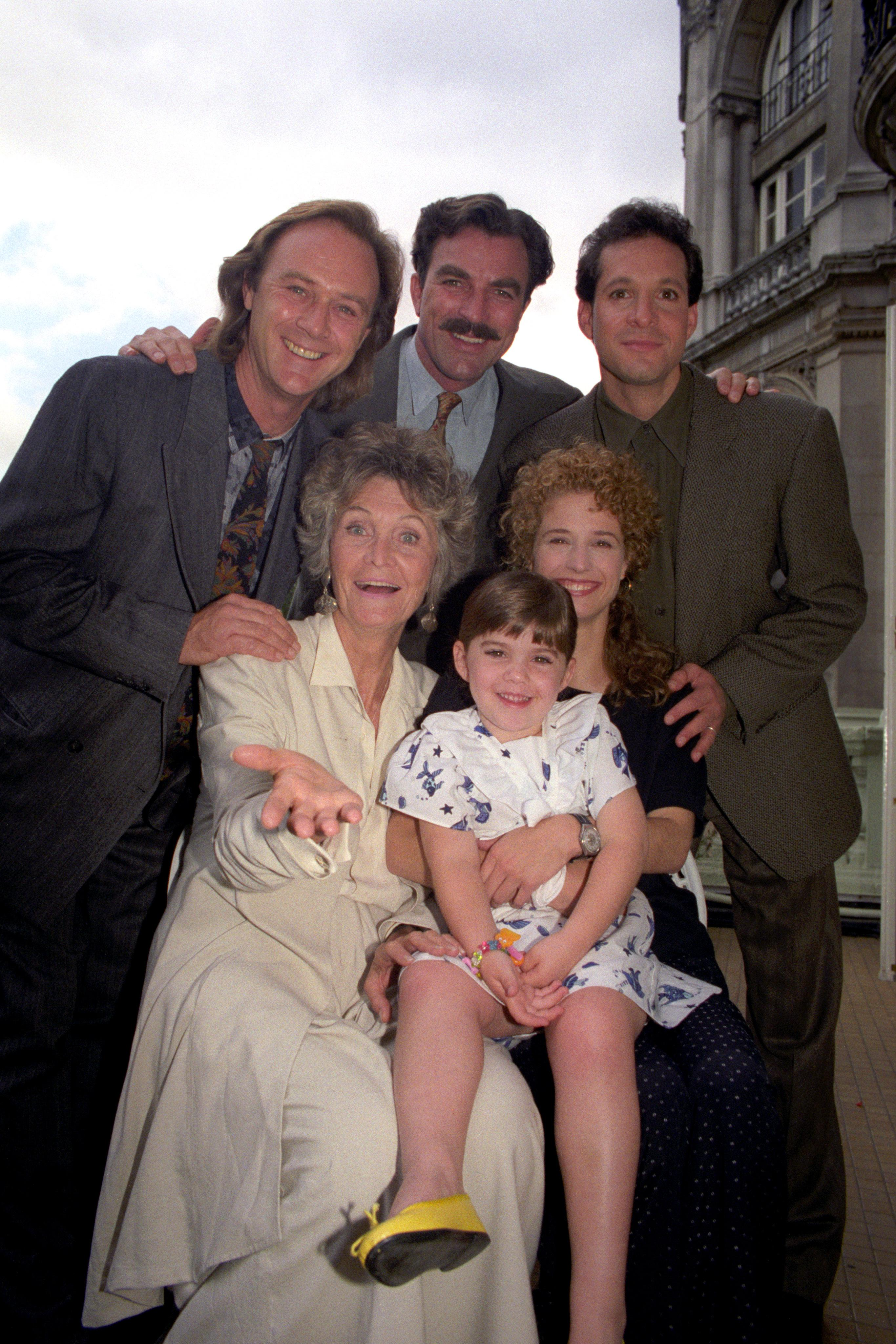 """The cast of the film """"Three Men and a Little Lady"""" in London before shooting for three weeks on location in Stratford-upon-Avon. From left (back row) Christopher Cazenove, Tom Selleck and Steve Guttenberg. Front Row: Sheila Hancock, Robin Wiseman (child) and Nancy Travis (right). (Photo by Sean Dempsey/PA Images via Getty Images)"""