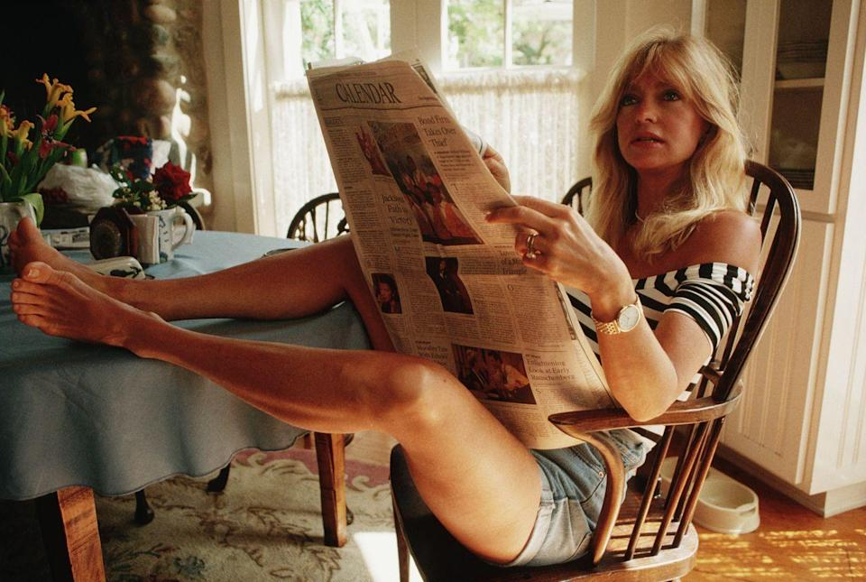 <p>Goldie Hawn is timeless. Wearing jean shorts and a striped t-shirt, the actress casually reads her morning paper. </p>