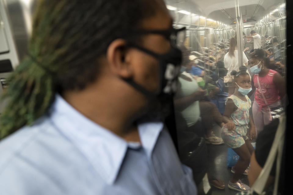 Desmond Hill, a vaccinated MTA conductor, looks out into a packed passenger cabin through the crew cab door as he works the N subway line from Brooklyn's Coney Island to Queen's Astoria-Ditmars neighborhoods, Friday, Aug. 13, 2021, in New York. As New York City recovers from the COVID-19 pandemics' peak ridership on the aging transit system continues to rebound as authorities encourage mask and social distancing protocols to stem further transmission of the virus. (AP Photo/John Minchillo)