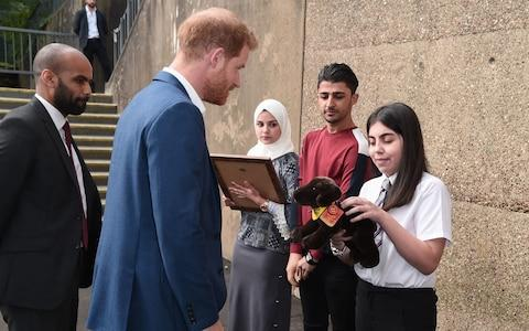 The Duke of Sussex receives a toy dog as a gift from 14-year-old Aleyna Genc - Credit: PA