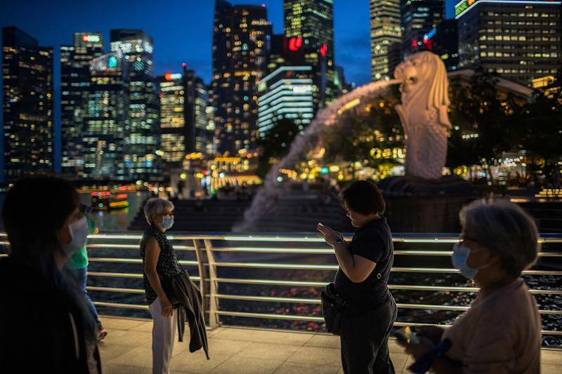 SINGAPORE - 2020/02/12: People wearing protective surgical masks visit the Merlion Park, a major tourist attraction in Singapore. Singapore declared the Coronavirus outbreak alert as Code Orange on February 7, 2020. (Photo by Maverick Asio/SOPA Images/LightRocket via Getty Images)