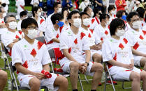 Olympic torchbearers wearing face masks sit and wait for their turn in Kanazawa, central Japan, Monday, May 31, 2021. Japan, seriously behind in coronavirus vaccination efforts, is scrambling to boost daily shots as the start of the Olympics in July closes in. (Kazushi Kurihara/Kyodo News via AP)