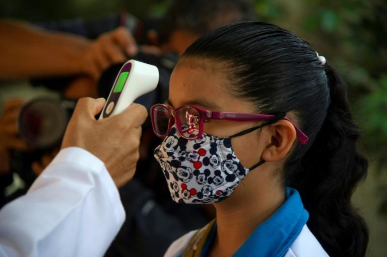 A girl has her temperature measured before returning to a classroom in Mexico City for the first time in more than a year