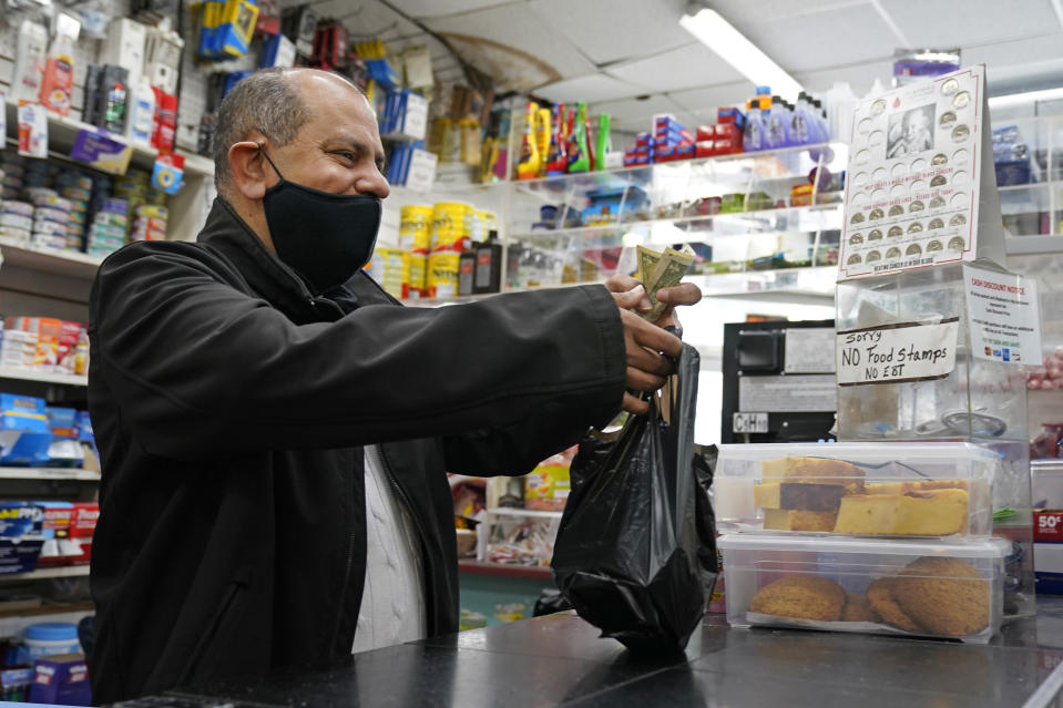 Bodega owner Francisco Marte assists a customer, Wednesday, Feb. 10, 2021, at his store in the Bronx borough of New York. Marte heads up the Bodega and Small Business Group, which represents bodegas in New York. (AP Photo/Kathy Willens)