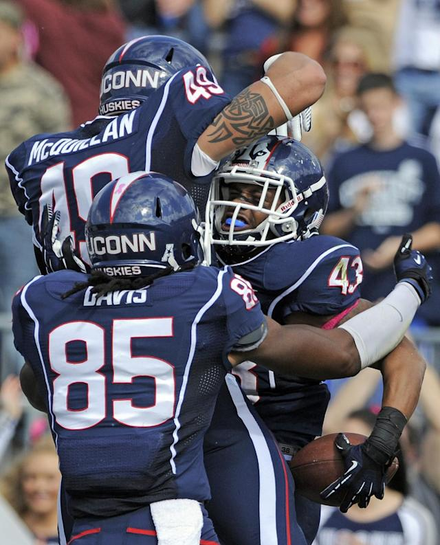 Connecticut running back Lyle McCombs (43) celebrates his 52-yard touchdown run with teammates Sean McQuillan (49) and Geremy Davis (85) during the first half of an NCAA college football game against South Florida in East Hartford, Conn., on Saturday, Oct. 12, 2013. (AP Photo/Fred Beckham)