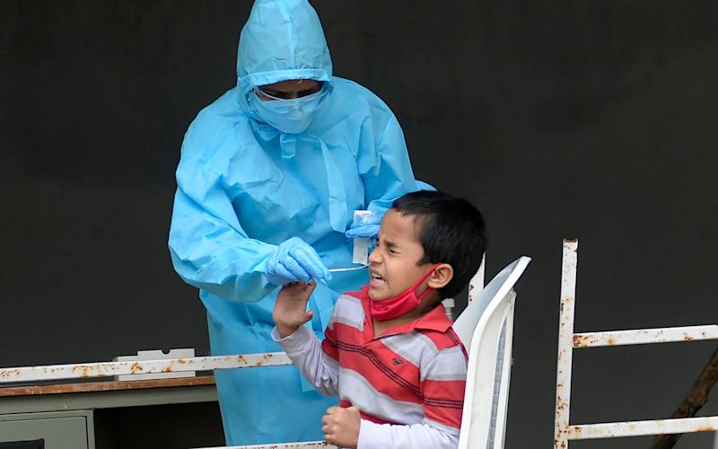 Hyderabad, India: A child reacts as a health worker collects a swab sample for a Covid-19 test as India reported its six millionth case on September 28 - AFP