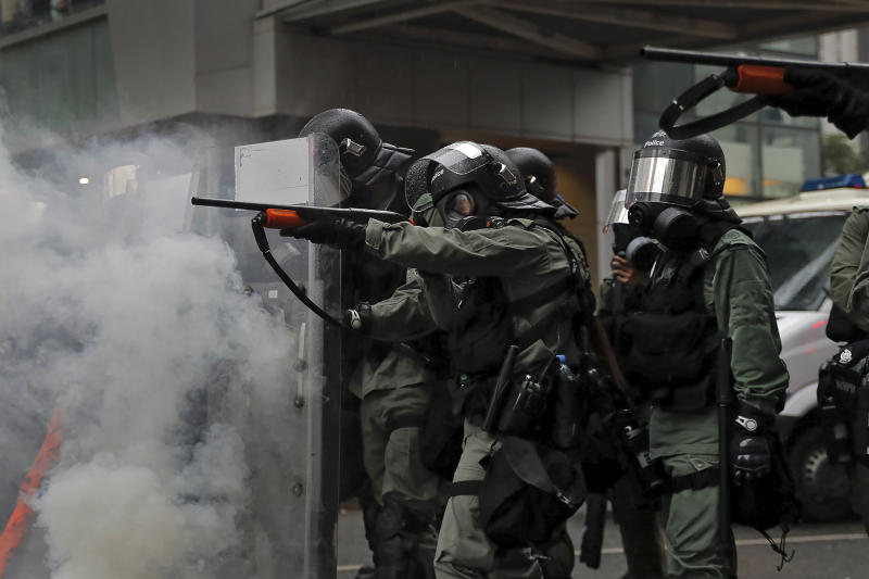 Riot policemen point weapons during a confrontation with demonstrators during a protest in Hong Kong, Sunday, Aug. 25, 2019. Hong Kong police have rolled out water cannon trucks for the first time in this summer's pro-democracy protests. The two trucks moved forward with riot officers Sunday evening as they pushed protesters back along a street in the outlying Tsuen Wan district. (AP Photo/Kin Cheung)