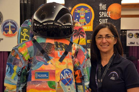 Astronaut Nicole Stott poses with a suit created by The Space Suit Art Project, a campaign to raise awareness of childhood cancer by MD Anderson Cancer Center, NASA and ILC Dover.