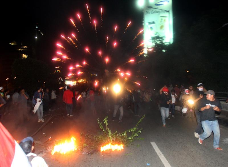 Protesters run as police fires firecrackers to disperse them during a protest against the government's plan to raise fuel prices outside the parliament in Jakarta, Indonesia, Friday, March 30, 2012. The Indonesian government plans to raise fuel prices by about 33 percent next month to avoid a budget deficit due to expensive fuel subsidies. (AP Photo/Achmad Ibrahim)