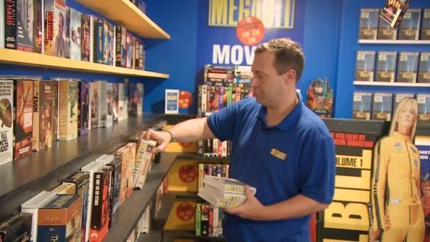 Corey Lynch turned his basement into a virtual video store, lined with VHS tapes, a front counter and, of course, snacks.  (CBC - image credit)