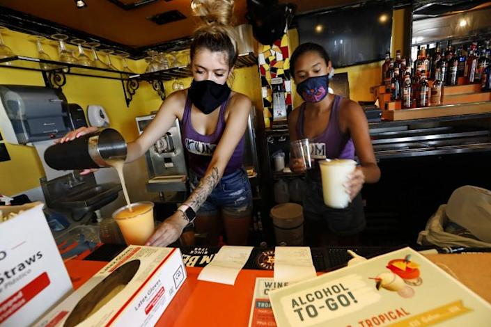 GALVESTON, TEXAS-JULY 3, 2020-Nila White, 20, left, and Brooklin Lafong, 22, right, stay busy making to-go cocktails to go at The Shot, a popular restaurant and bar in Galveston, Texas. Alcohol to-go was just legalized in Galveston on July 3, 2020, due to the pandemic. The beaches are closed on Galveston island for the 4th of July weekend, and there is a mandatory mask order in place due to the coronavirus Covid-19, but that hasn't stopped people from visiting this beach city. (Carolyn Cole/Los Angeles Times)