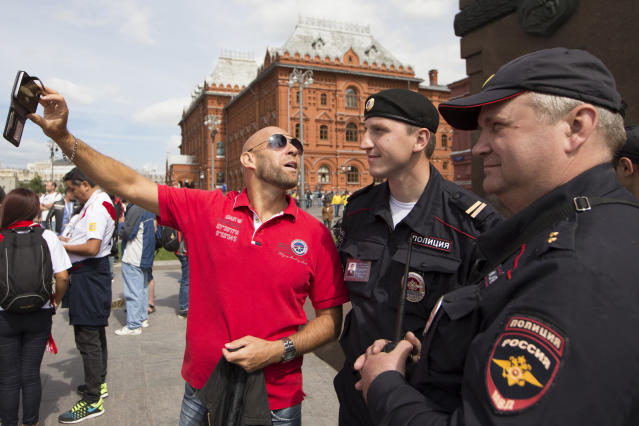 A Sweden soccer fan takes a selfie with Russian police officers near Red Square in Moscow, Russia, Thursday, June 14, 2018. Scalpers are still very visible at the World Cup, despite FIFA and Russia's claims they've cracked down on illicit ticket sales. (AP Photo/Alexander Zemlianichenko)
