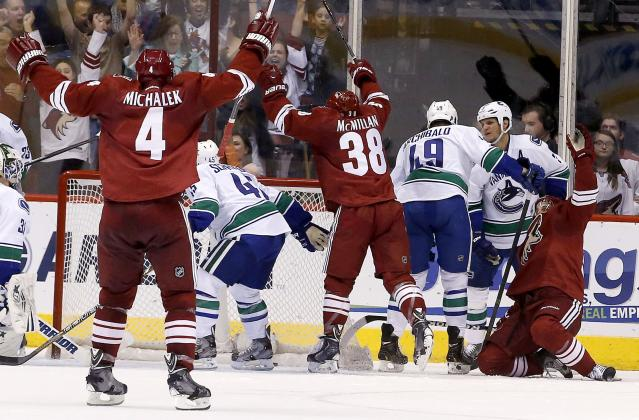 Phoenix Coyotes' Zbynek Michalek (4), of the Czech Republic, and Brandon McMillan (38) raise their ams in celebration as teammate Antoine Vermette, far right, scores a goal while Vancouver Canucks' Darren Archibald (49), Jordan Schroeder (45) and Kevin Bieksa, second from right, look for the puck during the first period of an NHL hockey game on Tuesday, March 4, 2014, in Glendale, Ariz. (AP Photo/Ross D. Franklin)
