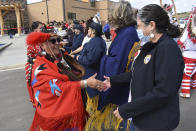 In this Wednesday, May 19, 2021, photo, Clarine DeGroot, left, of the Enemy Women Society traditional group is seen shaking the hand of a woman from the American Legion at an event marking the opening of the MHA Nation Interpretive Center, a cultural center and museum on the Fort Berthold Indian Reservation in New Town, North Dakota. The $30 million cultural center in New Town pieces together the tribes' fractured past through displays and artifacts. (AP Photo/Matthew Brown)