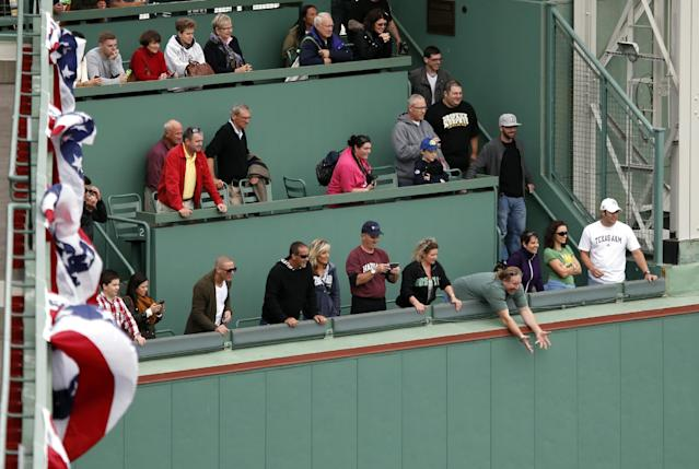 A fan reaches over the Green Monster wall hoping for a baseball, during a Boston Red Sox workout at Fenway Park in Boston, Thursday, Oct. 10, 2013, as the team prepares for Game 1 of the AL championship series on Saturday. (AP Photo/Elise Amendola)