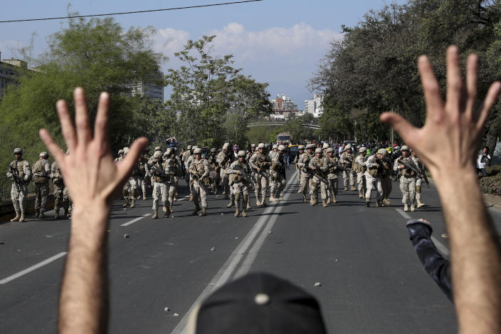 A demonstrator holds up his hands toward advancing soldiers during a protest as a state of emergency remains in effect in Santiago, Chile, Sunday, Oct. 20, 2019. Protests in the country have spilled over into a new day, even after President Sebastian Pinera cancelled the subway fare hike that prompted massive and violent demonstrations. (Photo: Esteban Felix/AP)