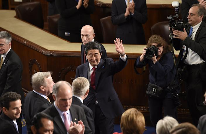 Japanese Prime Minister Shinzo Abe waves before he addresses a joint session of Congress at the U.S. Capitol in Washington, D.C., on April 29, 2015.