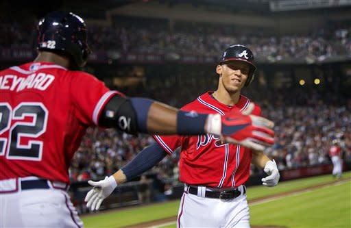 Atlanta Braves' Andrelton Simmons, right, high-fives teammate Jason Heyward after hitting a home run in the fifth inning of a baseball game against the Arizona Diamondbacks, Friday, June 28, 2013, in Atlanta. (AP Photo/David Goldman)