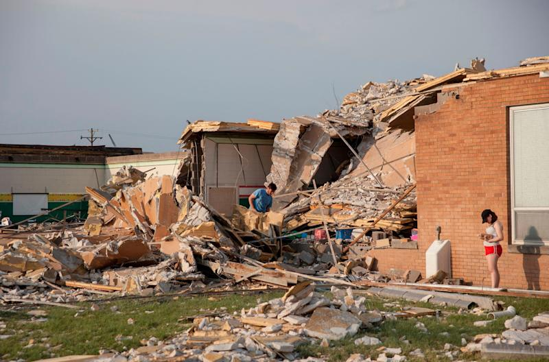 Damage at a school in Dayton, Ohio, is surveyed on Tuesday, after powerful tornadoes ripped through the area and caused at least one death. (Photo: SETH HERALD via Getty Images)