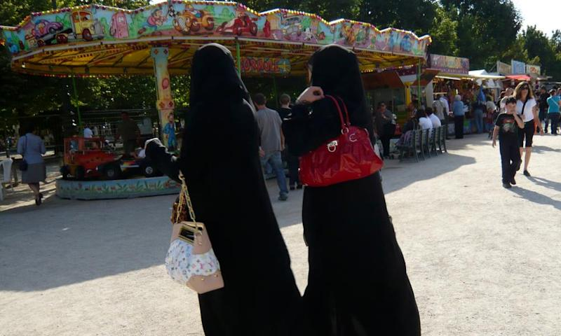 Women wearing niqabs walk in the Tuileries in Paris