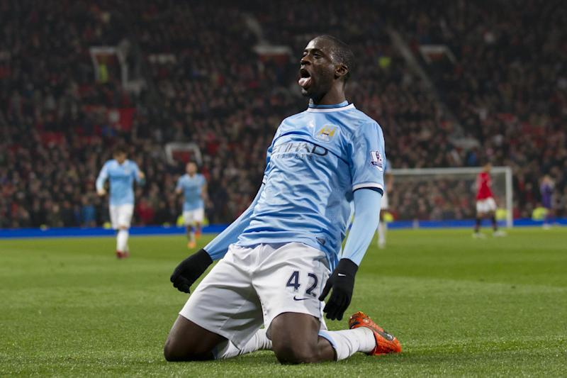 Manchester City's Yaya Toure celebrates after scoring against Manchester United during their English Premier League soccer match at Old Trafford Stadium, Manchester, England, Tuesday, March 25, 2014. (AP Photo/Jon Super)