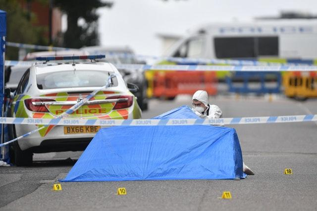 A police forensic officer looks under a small blue police tent covering an area of road in Irving Street in Birmingham (Jacob King/PA)