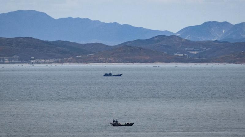 Unidentified fishing boats before the North Korean coastline from a viewpoint on the South Korea-controlled island of Yeonpyeong near the disputed waters of the Yellow Sea at dawn.