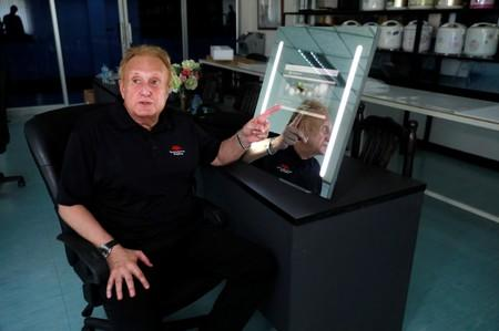 Larry Sloven shows a touch mirror that can be used as a tablet, at a factory in Bangkok