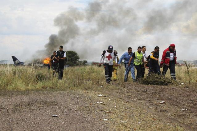 <p>In this photo released by Red Cross Durango communications office, Red Cross workers and rescue workers carry an injured person on a stretcher, right, as airline workers, left, walk away from the site where an Aeromexico airliner crashed in a field near the airport in Durango, Mexico, Tuesday, July 31, 2018. (Photo: Red Cross Durango via AP) </p>