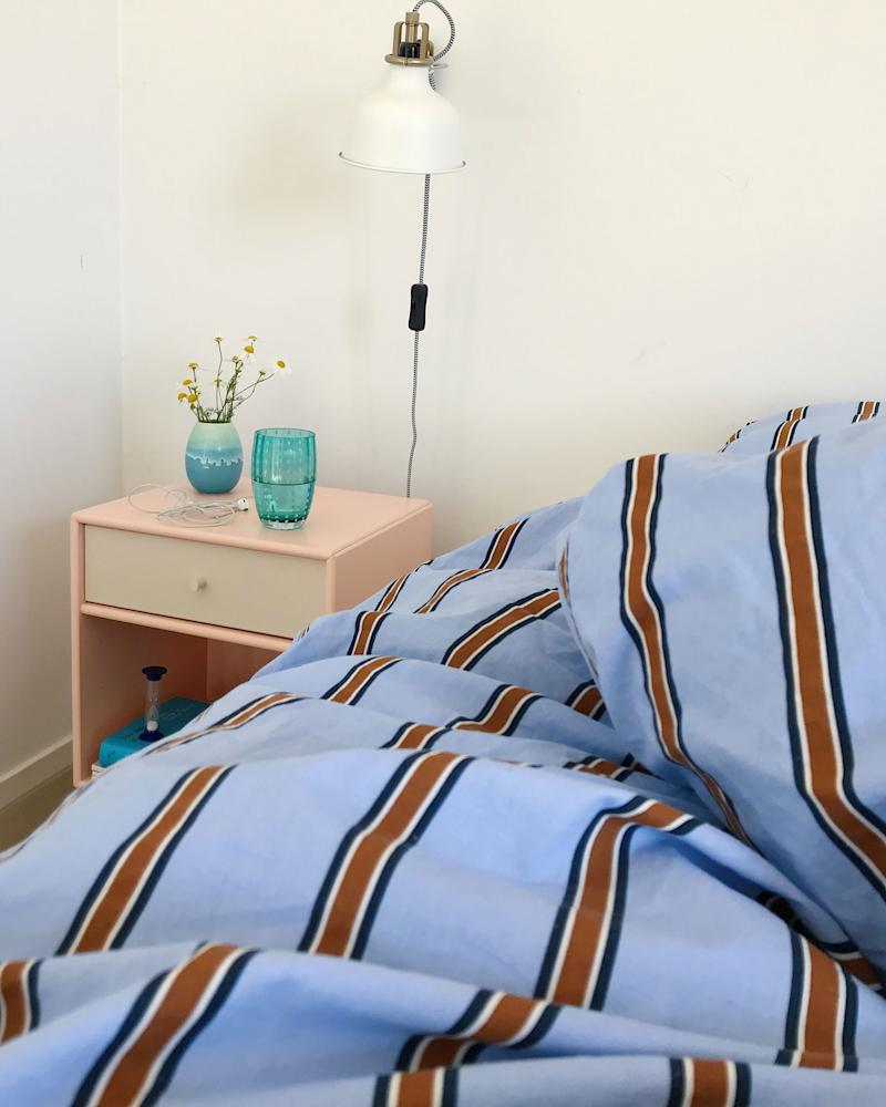 """Go for unexpected color combos: """"I tend to pick warm pastels like dusty blues and pinks to make the space inviting,"""" says Lisbeth. """"Then I look for something that will add contrast, like a bright turquoise vase or a stripe."""" In her bedroom, Lisbeth paired a soothing blush Montana Furniture nightstand with menswear-inspired H&M Home bedding. How to get the look? Choose colors opposite each other on the color wheel, then pick a hue a couple notches to either side for a twist."""