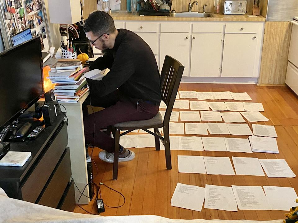 Lakayana Drury works on his autobiographical poetry manuscript, arranged on the floor of his Portland, Ore., apartment.