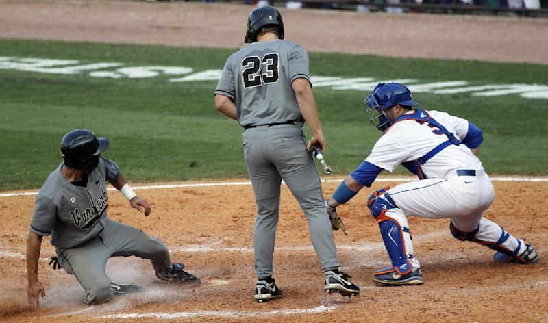 Vanderbilt's Anthony Gomez, left, steals home in the ninth inning of their 8-6 win over Florida in an NCAA college baseball game during the Southeastern Conference tournament in Hoover, Ala., Saturday, May 26, 2012. At right is Florida catcher Mike Zunino.  (AP Photo/Dave Martin)