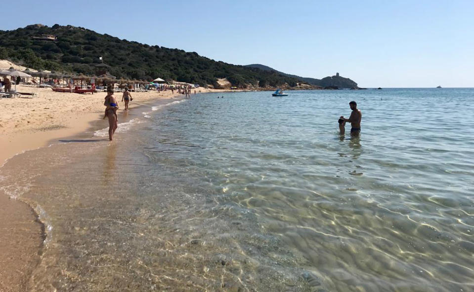 In this June 29, 2019 photo, people enjoy the white sand and pristine waters of Chia beach, on the Italian island of Sardinia, Italy. A French couple could face up to six years in jail for taking around 40 kg (88.1lbs) of white sand from Chia beach on the Italian island of Sardinia. (AP Photo/Karl A.Ritter)