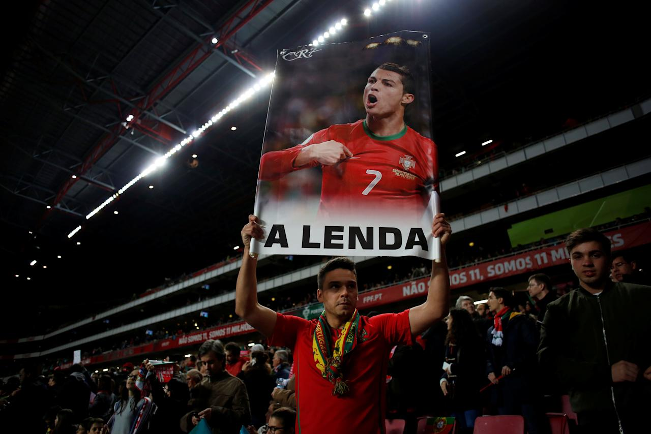 "Football Soccer - Portugal v Hungary - World Cup 2018 Qualifiers European Zone - Group B - Luz Stadium, Lisbon, Portugal - 25/03/17 - A man holding a poster of Cristiano Ronaldo with the word ""The Legend"" before the game. REUTERS/Pedro Nunes EDITORIAL USE ONLY. NO RESALES. NO ARCHIVE."