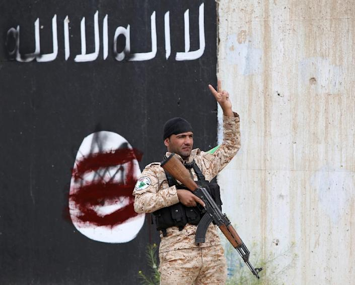 A member of the Iraqi security forces flashes the sign for victory in front of a defaced Islamist flag in Tikrit on April 1, 2015 (AFP Photo/Ahmad Al-Rubaye)