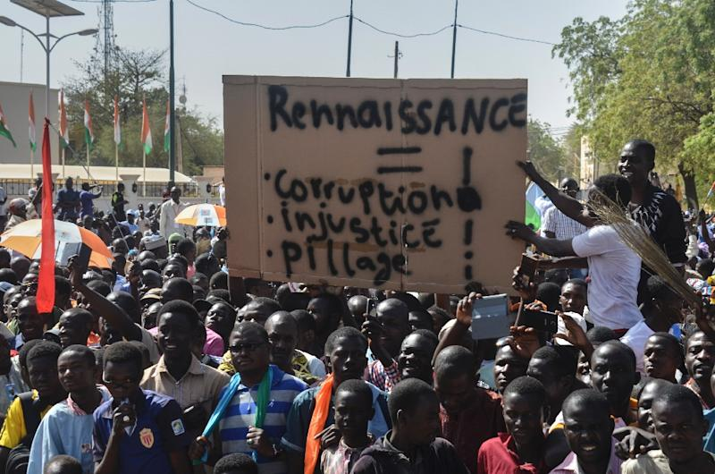 "Members of the Niger Front for the Restoration of Democracy and the Defence of the Republic, hold a placard reading ""Rebirth, corruption, injustice, looting"", as they protest in Niamey on March 4, 2017"